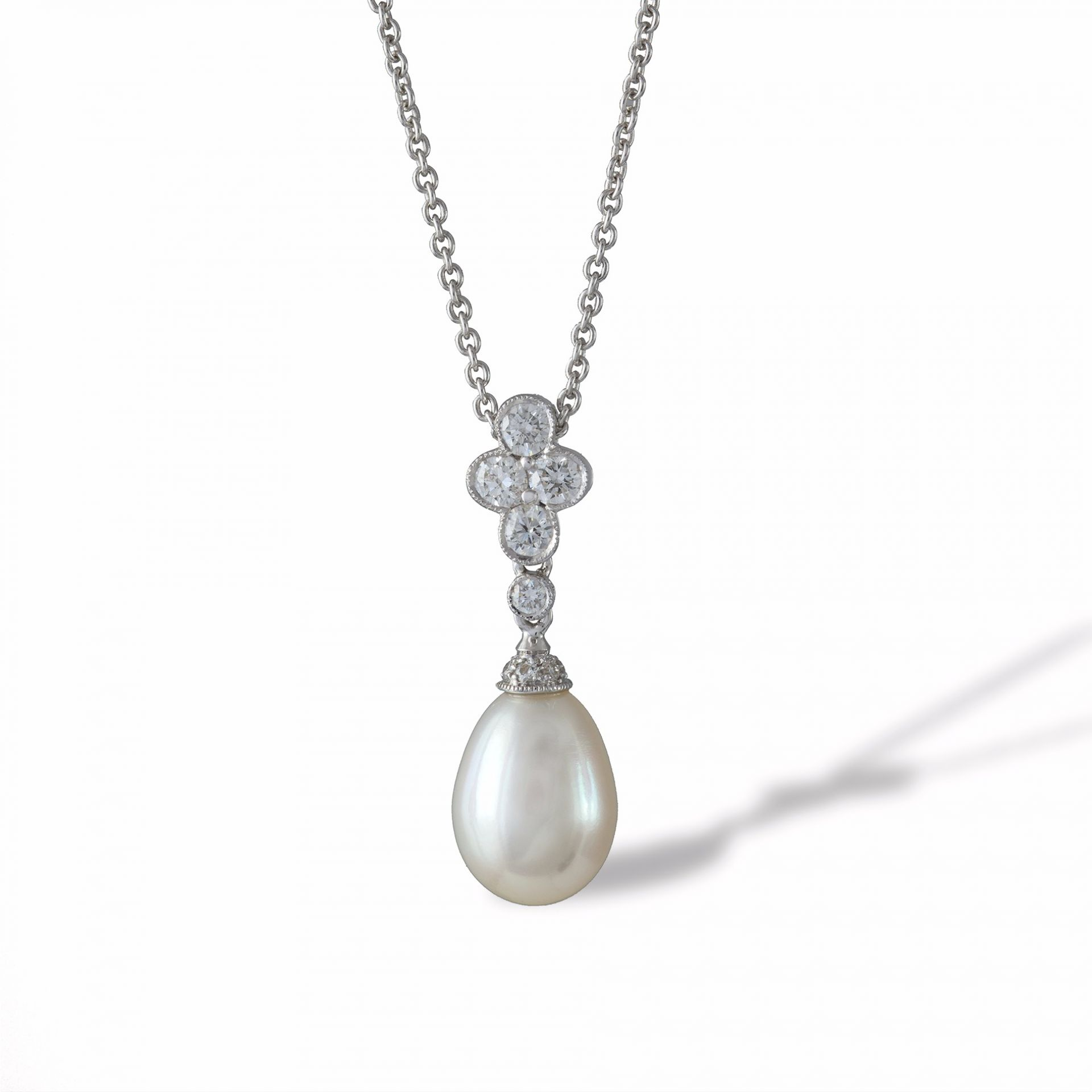 A pearl and diamond drop pendant with chain