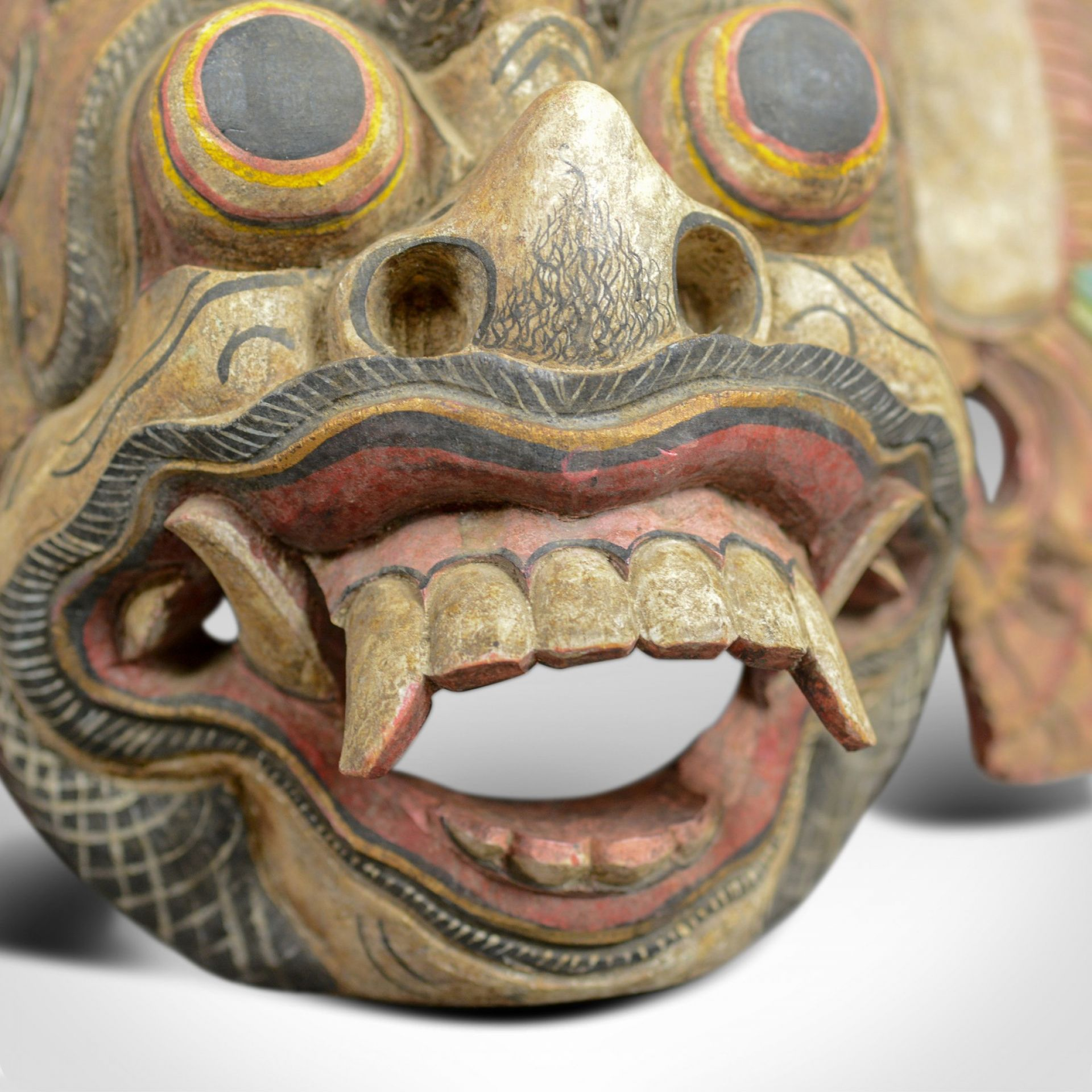 This is a Balinese 'Barong' carved mask. A decorative painted wooden face mask,