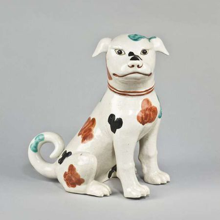 A porcelain dog seated on its haunches decorated in the Kakiemon palette
