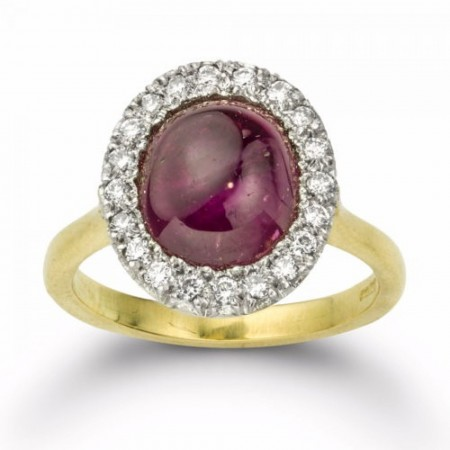 A cabochon burmese star ruby and diamond cluster ring